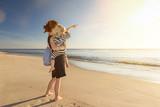 Mutter mit Kind auf dem Arm steht am Strand und schaut in den Sonnenuntergang