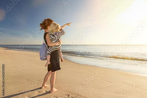 Leinwandbild Motiv Mutter mit Kind auf dem Arm steht am Strand und schaut in den Sonnenuntergang