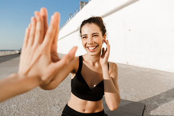 Cheerful young fitness woman giving high five