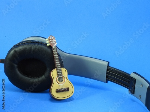 Close-up of a miniature acoustic guitar propped up on a black and silver headphone. Blue background. - 260264011