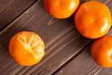 Group of three whole fresh orange mandarine one fruit is half peeled flatlay on brown wood