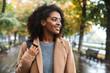 Quadro Beautiful young african woman wearing coat walking outdoors