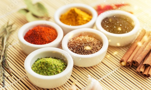 Various colorful spices in bowls on wooden table © BillionPhotos.com