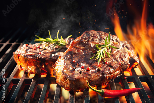 Beef steaks sizzling on the grill - 260271235