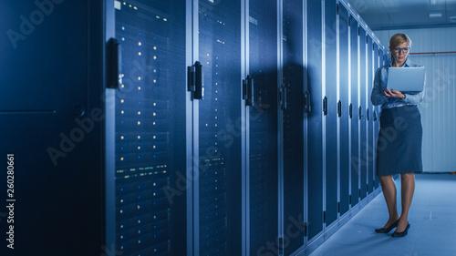 In Data Center: Female IT Technician Running Maintenance Programme on a Laptop, Controls Operational Server Rack Optimal Functioning. Modern High-Tech Telecommunications Operational Super Computer.