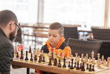 Boy playing chess with father on a family chess tournament at a school.