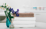 Tranquil scene with towels and flowers at spa. White towels, aromatherapy and spa treatment