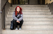 Leinwandbild Motiv Homeless girl, Young beautiful red hair girl sitting alone outdoors on the stairs of the building with hat and shirt feeling anxious and depressed after she became a homeless person