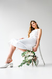 low angle view of young woman in dress sitting on chair and holding bouquet of flowers with eucalyptus leaves on white
