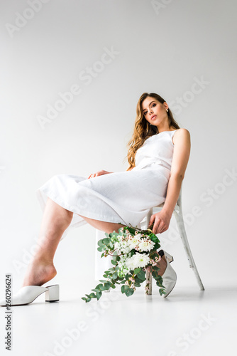 low angle view of young woman in dress sitting on chair and holding bouquet of flowers with eucalyptus leaves on white © LIGHTFIELD STUDIOS