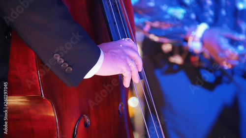 A jazz concert in the concert hall. A man in costume playing cello - 260297045