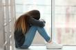 Leinwandbild Motiv Upset teenage girl sitting at window indoors. Space for text