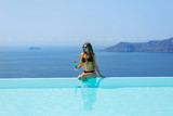 Young woman sitting on the edge of the pool