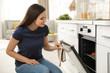 Leinwandbild Motiv Beautiful woman opening door of oven with baked buns in kitchen