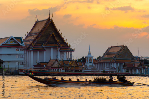 fototapeta na ścianę Tourist long trail boat is running through the temple during sunset in Bangkok.