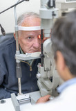 Male optometrist checking the eyesight of his patient and choosing the lens for her in clinic after.retinal thrombosis - 260313067