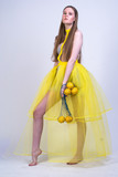 young girl in yellow dress and with lemons