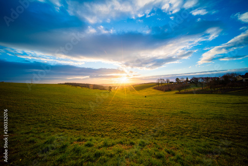 Sunrise in spring field at early morning