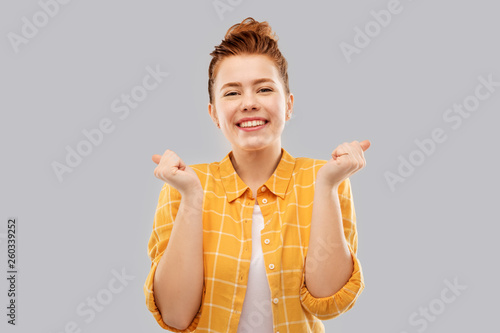 achievement, emotions and people concept - happy smiling red haired teenage girl in checkered shirt celebrating success over grey background © Syda Productions