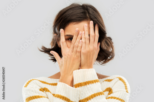 Leinwandbild Motiv people concept - happy smiling young woman in striped pullover closing face with hands and looking by one eye through her fingers over grey background