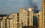 Black smoke of a fire above buildings in a residential part of a city