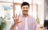 count and people concept - smiling young man showing five fingers over office room background