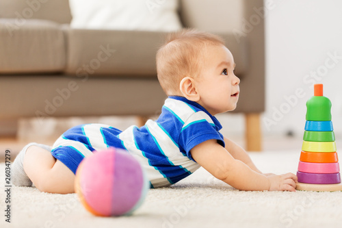 babyhood, childhood and people concept - sweet little asian baby boy playing with toy ball - 260347279