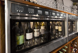alcohol, technology and storage concept - close up of wine bottles storing in dispenser at bar or restaurant