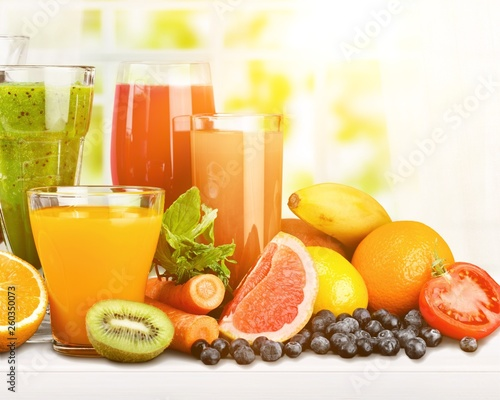 Leinwanddruck Bild Tasty fruits  and juice with vitamins on background