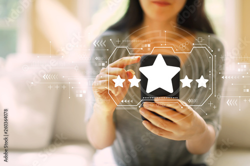 Leinwandbild Motiv Five star rating with woman using her smartphone in a living room