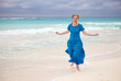 The woman in a long blue dress goes on the sea coast Cayo Largo island, Cuba