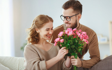 happy loving couple. husband gives his wife flowers at home .