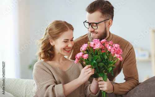 happy loving   couple. husband gives his wife flowers at home    . - 260376227