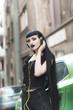Leinwandbild Motiv Urban goth girl listening to her favourite music over her big headphones, street in a city surroundings