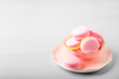 Pink yellow macaroons cakes on gray blue table background, place for text, trendy minimalism style, selective focus
