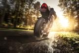 Motorrad bei Sonnenschein auf einer Waldstraße