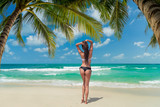 Woman enjoying her holidays on the tropical beach i