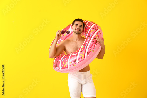 Leinwandbild Motiv Handsome man with inflatable ring on color background