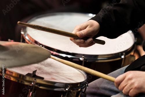 The hands of a man playing a drum set in dark colors - 260469812