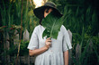 Stylish girl in linen dress holding big green leaf at face at wooden fence and grass. Portrait of boho woman in hat posing with leaf in summer countryside in evening. Atmospheric moment
