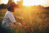 Stylish girl in linen dress gathering flowers in rustic straw basket, sitting in poppy meadow in sunset. Boho woman in hat relaxing in warm evening sunlight in summer field. Space for text