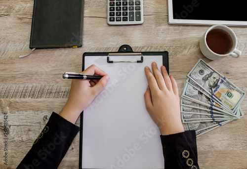 female hands with pen, dollars s calculator on the table © Tania