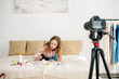 Teenage kid sitting on bed with cosmetics in front of video camera