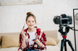 Smiling teenager in checkered shirt holding brush and eye shadows in front of video camera