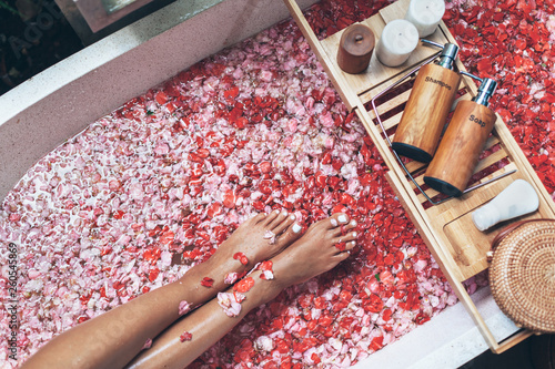 Leinwanddruck Bild Female legs in bathtub with flower petals and beauty products on wooden tray