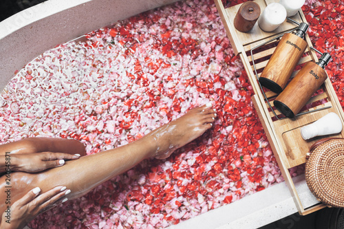 Female legs in bathtub with flower petals and beauty products on wooden tray © Alena Ozerova
