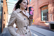 Leinwanddruck Bild - Coffee on the go. Beautiful young woman holding coffee cup and smiling while walking along the street