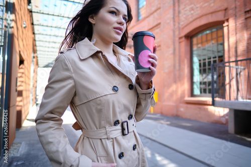 Leinwanddruck Bild Coffee on the go. Beautiful young woman holding coffee cup and smiling while walking along the street