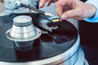 Woman putting needle on vinyl record on turntable