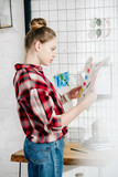 Side view of pensive teenager in checkered shirt looking at drawing
